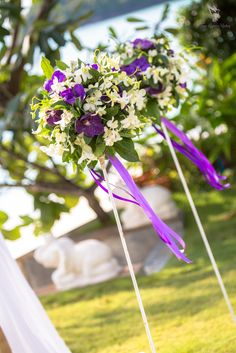 Deep purple vanda orchids with white orchids and trailing purple ribbon for this aisle decoration.