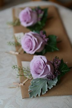 Lavender colored boutonniere of lilac Ocean Song roses, senecio, heather, thlespi and ivy leaves.