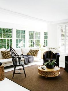 House tour: an Australian landscape architect's serene New York home: In the sitting room, a Wolf Home 'Alison' sofa and 'Ektorp Tullsta' armchairs from Ikea are combined with an antique Windsor chair from Spruce Design + Decor. The hand-carved Indian mango-wood coffee table is from West Elm.
