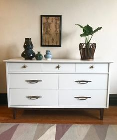 This petite mid-century modern 6 drawer dresser made by Kroehler has been refinished in bright white with gold starburst details on the top drawers.