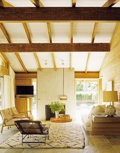 An Architectural Living Room:   The architecture is the star of the decor in this room, where exposed wood, a vaulted ceiling, a stone floor, and an impressive stucco chimney frame just a few midcentury modern furnishings. Room by Form Architecture and Interiors.