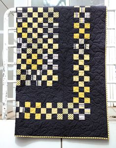 This modern quilt pattern features 9 patch quilt blocks that create a checkerboard in the quilt center with a checkerboard border.