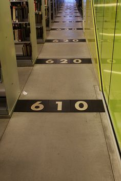 The Seattle Central Library has floor mats throughout the Books Spiral labeled with Dewey Decimal System numbers to help people find the items on each floor. Environmental Graphic Design, Environmental Graphics, Seattle Central Library, Restaurant Hotel, Library Signage, Wayfinding Signs, Floor Graphics, Signage Design, Banner Design