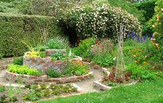 Here is my finished brick herb spiral, hugged by vegetable beds. Don't look too closely at the mortaring!