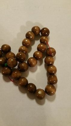 "Add these unique Round Wooden Beads to your jewelry making collection. The bead strand is 15"" long and each bead is 10mm in size approximately."
