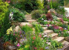 jardin de rocaille avec des fleurs colorées et escalier extérieur en pierre naturelle