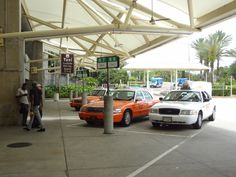 Orange and white Ford Crown Vic taxis at Orlando International Airport in Florida.
