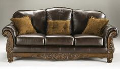 Buy Ashley North Shore Stationary Sofa with Top-Grain Leather Upholstery 3 Pillows Included Carved Details and Rolled Arns in Dark - Topvintagestyle.com ✓ FREE DELIVERY possible on eligible purchases