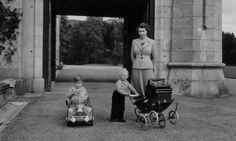 """Queen Elizabeth II with children Prince Charles & sister Princess Anne during playtime for the little royals. Published in """"Hello!"""" magazine."""