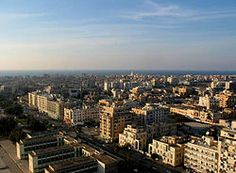 Downtown Benghazi... Benghazi is the second largest city in Libya, the largest city in the region of Cyrenaica, and the former joint capital of Libya. As of 2014, the city is Libya's de facto legislative capital as it houses the country's parliament, the Majlis al Nuwwab.[11] The wider metropolitan area (which includes the southern towns of Gimeenis and Suluq) is also a district of Libya. The port city is located on the Mediterranean Sea.