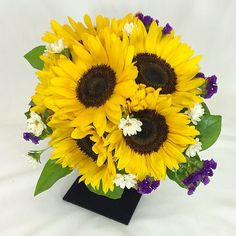 Brides bouquet of beautiful sunflowers, with some white Matsumoto asters & purple status.