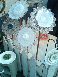 Yard Art Glass Flowers...my cousins made these by raiding flea markets and yard sales and in the center of theirs they put votive candle holders and hot glues glass stones in the center :) too cute!