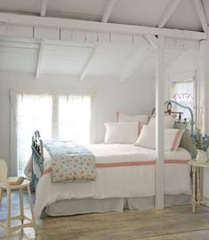 The mostly white bedding in this Florida cottage creates a cohesive (rather than choppy) look. A few red stripes and the floral coverlet add just enough pattern to bring some life to the room.   - CountryLiving.com