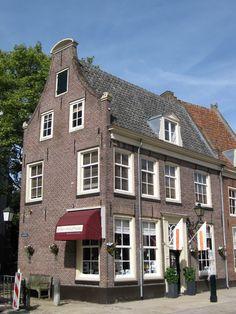 Hoog huis, gepleisterd in klokgevel, uitlopend zadeldak Marktstraat 15 naast de Grote kerk.