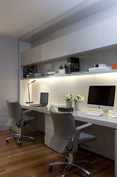 Small home office for two. Side by side arrangement. Minimalist and modern design with wooden flooring. White tabletop and cabinets. Decorating tips for home offices. #interiordesign #homeoffice #homeworkers