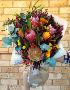 Native bouquet with proteas, snapdragons, roses, leucadendrons, billy buttons and hypericum berry.