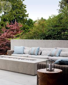 Chic patio boasts a concrete bench lined with gray outdoor cushions and blue and gray outdoor pillows facing a long concrete fire pit. Outdoor Sectional, Sectional Sofa, Tommy Bahama Beach Chair, Outdoor Furniture, Outdoor Decor, Fire Pit Table And Chairs, Adirondack Chairs For Sale, Home Decor, Homemade Home Decor