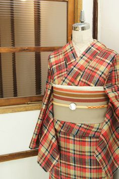 キャラメルベージュとパウダーレッド、クリームイエローとディープブルー、白、黒などの色糸で織り出されたチェックデザインにエスニックな飾り織りがさりげないアクセントになったナチュラル・モダンなウールの単着物です。