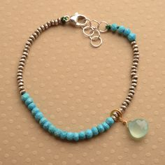 Blue turquoise stones are strung on silk thread with hill tribe silver beads to create this special bracelet. Blue is connected with the fifth or throat chakra. Hanging from the bracelet is a gorgeous