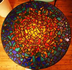 Mosaic table... Glass file and black grout... Looks like stained glass!