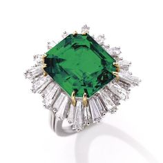 EMERALD AND DIAMOND RING The emerald-cut emerald weighing 12.42 carats, framed by 32 alternating tapered baguette diamonds weighing approximately 5.00 carats, mounted in platinum and gold