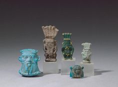 An Egyptian worn amulet of Bes, a green Bes, a blue and yellow Bes, an Egyptian blue amulet of a bearded man and a blue Bes amulet with mane. I Bonhams