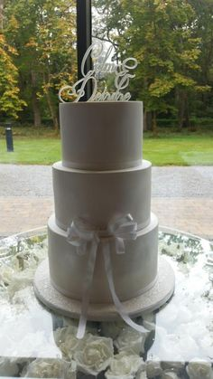 So the bride wanted pretty and the groom wanted funny. … three double barrel tiers with sharp edges and nothing to hide behind except a skinny ribbon and bow…. The fun was around the back of the cake where the groom's 4 off road jeep was leaving...