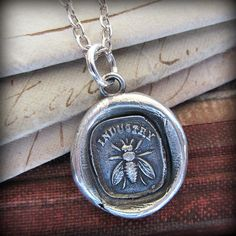"""Pictured is a honey bee with the word """"INDUSTRY"""" above it, this charm is a reminder of how we all prosper from teamwork and community spirit."""