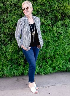 A polished casual outfit featuring a knit black and white knit summer jacket, jeans, and silver-toned jewelry and slide sandals.