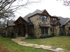 Noble Classic Homes... love the mixed stone and thick wooden beams