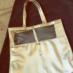 """Gold bag with clear cut out from Neiman Marcus Simple Neiman Marcus (unlabeled) gold bag with clear cutouts. Great for beach or pool. 16"""" by 14"""" with handle. One interior pocket. Never used. Happy to bundle. Just ask. ❣ Neiman Marcus Bags Totes"""