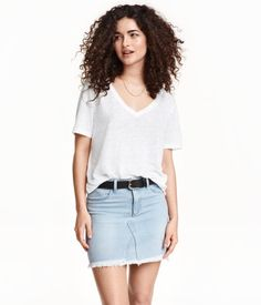 Short skirt in washed denim with a zip fly. Mock front pockets, regular back pockets, and a frayed, raw-edge hem.