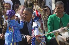 US President Barack Obama (C) talks with Native American performers as he sits with First Lady Michelle Obama (R) during the Cannon Ball Flag Day Celebration in Cannon Ball, North Dakota, June 13, 2014.       AFP PHOTO / Jim WATSON        (Photo credit should read JIM WATSON/AFP/Getty Images)