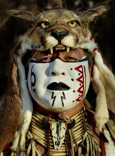 Native man in a traditional mountain lion headdress at the Stanford Powwow, California, USA