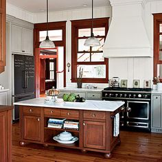 Wood trim kitchen with grey cabinets, wood island lower cabinets and white walls