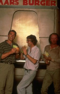 Just having a Mars burger, nothing special.    Arnold Schwarzenegger, Paul Verhoeven and an unnamed extra in full mutant make up, grabbing some din-dins on the set of Total Recall (1990).