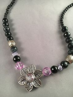 You'll love this black-beaded necklace with a silver-colored pendant with a soft purple center. Matching earrings