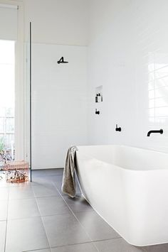 The choice of black tapware gives this glossy white bathroom a subtle but dynamic edge. Grey floor tiles add warmth and depth to the space Photographer: Derek Swalwell Stylist: Heather Nette King