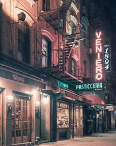 Fire escape stairs and neon signs, by Franck Bohbot.
