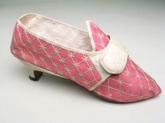 Shoes, England, 1770-1785, Deep pink glazed wool bound with cream silk ribbon, embroidered in all over diamond pattern in chain stitch in cream silk thread. Fastening with straps in cream glazed wool with buckle. Pointed toes. Heels covered with cream glazed wool.