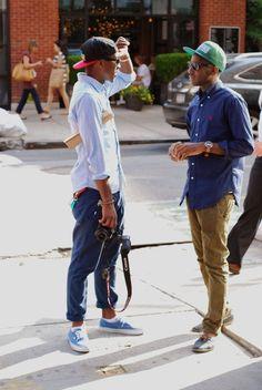 Comprar ropa de este look:  https://lookastic.es/moda-hombre/looks/camisa-de-manga-larga-azul-marino-pantalon-chino-marron-claro-nauticos-azules-gorra-de-beisbol-verde/1704  — Camisa de Manga Larga Azul Marino  — Gorra de Béisbol Verde  — Pantalón Chino Marrón Claro  — Náuticos de Ante Azules
