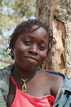 Daughter of Marie Toure, face of African girl, red blouse, jeans jacket, Guinea Bissau.