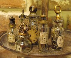 "Each little glass bottle is 2-inches high or less, and contains real, vintage watch parts (gears, springs, etc) topped off by broken clock parts and/or vintage brass fittings. The ""labels"" are real..."