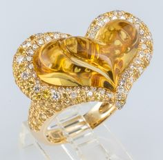 14k Gold ring featuring a smooth 12ct heart shaped citrine, measuring 20.0 x 12.3 mm. Citrine is surrounded by 2.9ct in yellow sapphires and 0.74ct in diamonds. Produced by designer Michael Christoff.  $1,299.99