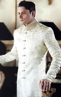 A Sherwani is a long coat, with a buttoned Nehru styled collar and has buttons through the length of the placket. The length is usually just below the knees and is worn with tight fitting pants or churidars.