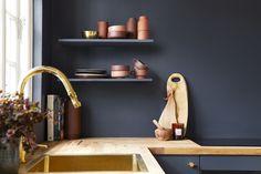 Et udsnit af et køkken med blå vægge og skabslåger i samme farve. PÅ hylderne står terrakotta kopper, kander og skåle. Op af væggen et organisk skærebræt.