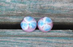 Puzetky+růžové+s+kytičkou+Nerezové+puzetky+vrůžové+se+světle+modrou+kytičkou.Jako+podklad+prosvítá+růžový+alabastr+a+modrobílá+kytička+plave+v+křišťálu.Velikost+vinutek+je+12+mm.