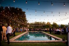 Gorgeous-looking summer pool party. Love the string lights!