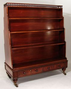 "Regency two-sided waterfall bookcase    A rare Regency two-sided mahogany waterfall bookcase, the galleried top over 4 graduated shelves above 2 real and 2 false drawers on faceted feet ending in brass casters. Circa 1820.    H. 56"" W. 46 1/2"" D. 22"""