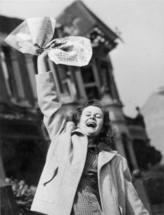 70 years ago: Historic VE Day celebration photos-Pat Burgess of Palmers Green, North London, waves a newspaper containing the news of Germany's surrender in World War II.